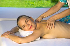 Smiling female enjoys in massage. Royalty Free Stock Photos