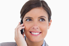 Smiling female entrepreneur on her cellphone. Close up of smiling female entrepreneur on her cellphone against a white background Royalty Free Stock Photo