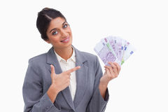 Smiling female entrepreneur pointing at money in her hand Stock Images
