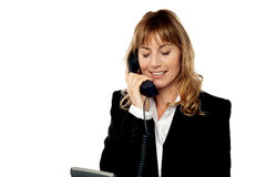 Smiling female executive attending phone call stock images