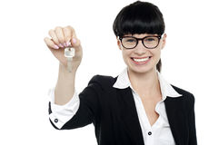 Smiling female executive handing over the key Royalty Free Stock Image