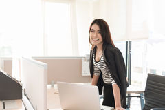 Smiling female executive leaning on desk in office Stock Photo