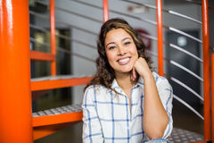 Smiling female executive sitting on staircase in office Royalty Free Stock Photo