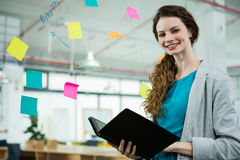 Smiling female executive standing with folder in creative office Royalty Free Stock Photography