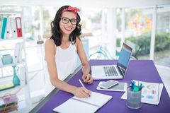 Smiling female executive writing in diary in office Royalty Free Stock Photography