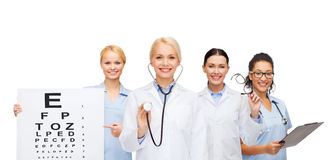 Smiling female eye doctors and nurses. Healthcare, vision and medicine concept - smiling female eye doctors and nurses with eye exam chart, glasses and clipboard Royalty Free Stock Photo