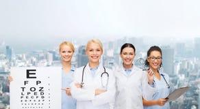 Smiling female eye doctors and nurses Royalty Free Stock Photos