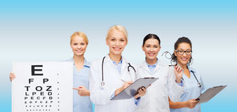 Smiling female eye doctors and nurses. Healthcare, vision and medicine concept - smiling female eye doctors and nurses with eye exam chart, glasses and clipboard Royalty Free Stock Image
