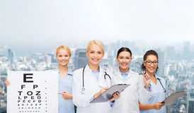 Smiling female eye doctors and nurses. Healthcare, vision and medicine concept - smiling female eye doctors and nurses with eye exam chart, glasses and clipboard Royalty Free Stock Images