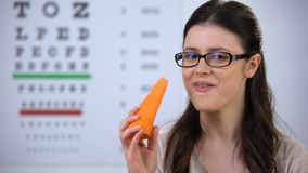 Smiling female in eyeglasses biting fresh carrot, useful vitamins and minerals. Stock footage stock video footage