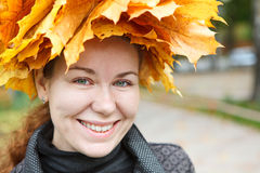 Smiling female face with yellow maples wreath Royalty Free Stock Photo
