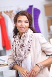 Smiling female fashion designer sitting at office Royalty Free Stock Images