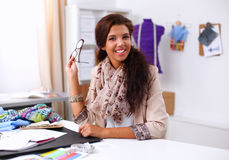 Smiling female fashion designer sitting at office Royalty Free Stock Photo