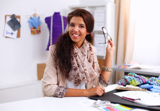 Smiling female fashion designer sitting at office Royalty Free Stock Image