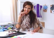 Smiling female fashion designer sitting at office Stock Photos