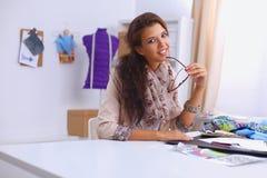 Smiling female fashion designer sitting at office Stock Photography