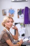 Smiling female fashion designer sitting at office Royalty Free Stock Photos