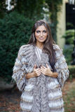 Smiling female fashion model posing in a fur coat outdoor Stock Photo