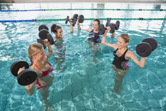 Smiling female fitness class doing aqua aerobics with foam dumbbells. In swimming pool at the leisure centre Stock Photography