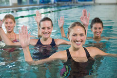 Smiling female fitness class doing aqua aerobics Royalty Free Stock Images
