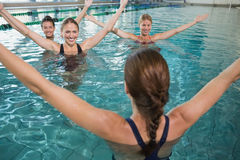 Smiling female fitness class doing aqua aerobics Royalty Free Stock Photo