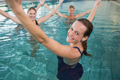 Smiling female fitness class doing aqua aerobics. In swimming pool at the leisure centre Royalty Free Stock Photos
