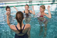 Smiling female fitness class doing aqua aerobics. In swimming pool at the leisure centre Stock Images