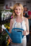 Smiling female florist holding watering can in flower shop Royalty Free Stock Photos