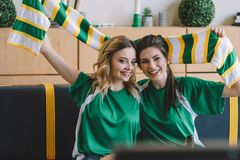 Smiling female football fans in green t-shirts and scarf celebrating during watch of soccer match. At home stock photo