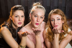 Smiling female friends blowing a kiss towards camera Royalty Free Stock Photo