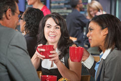 Smiling Female with Friends in Cafe Royalty Free Stock Photos