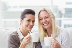 Smiling female friends having coffee in living room Stock Photography
