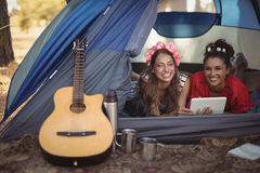 Smiling female friends relaxing in tent Stock Photography