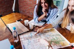 Smiling female friends sitting at desk planning their vacation looking for destinations on map stock photos