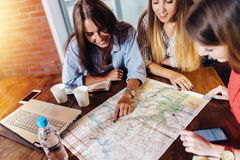 Smiling female friends sitting at desk planning their vacation looking for destinations on map.  Stock Photography