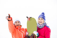 Smiling female friends with snowboard outdoors Stock Photo
