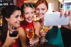 Female friends taking selfie with wine glass in night club royalty free stock photo