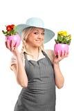 A smiling female gardener holding pots Stock Image