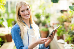 Smiling female gardener using digital tablet. Portrait of smiling female gardener using digital tablet at greenhouse Stock Photography