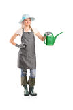Smiling female gardener with watering can stock photography
