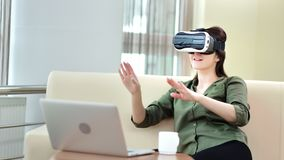 Smiling female gesticulating in modern virtual reality glasses in front of computer pc. Medium shot enthusiastic female enjoying vr hi-tech contemporary device stock video footage