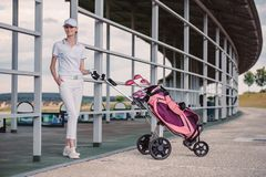 Smiling female golf player in while polo and cap with golf equipment. At golf course royalty free stock photography