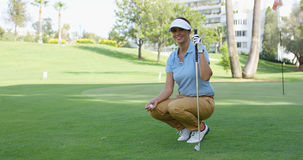 Smiling female golfer with brown hair crouches Stock Photo