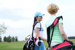 Smiling female golfer talking to friend at golf course Stock Images