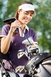 Smiling female golfer. Smiling woman on golf course with golf bag Stock Photo