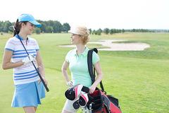 Smiling female golfers talking at golf course Royalty Free Stock Images