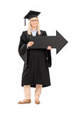 Smiling female in graduation gown holding a big black arrow Stock Images