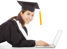 Smiling female graduation lying on floor with laptop Royalty Free Stock Photo