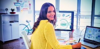 Smiling female graphic designer working in creative office. Portrait of smiling female graphic designer working in creative office stock photography