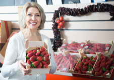 Smiling female grocery worker selling fresh strawberry at market Royalty Free Stock Photo